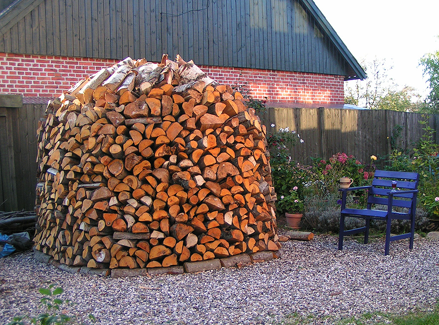 image of a large supply of firewood in a verdant garden